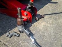 Chave pneumática com as porcas do pneu de carro Fotografia de Stock