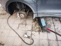 Chave pneum?tica com as porcas do pneu de carro do assoalho no elevador de jaque concreto do carro de lado e em uma parte de meta fotos de stock royalty free