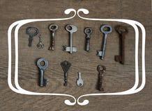 Chaves antiquados no fundo envelhecido de madeira com conceito do quadro Fotografia de Stock Royalty Free