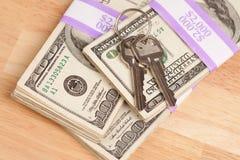 Chaves da casa na pilha de dinheiro imagem de stock royalty free