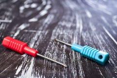 Chaves de fenda para reparar o encontro na tabela Trabalhos domésticos do ` s dos homens reparo Foto de Stock