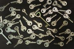 Chaves de prata em uma placa de madeira escura Tipos diferentes de chaves Chave ao coração Fotografia de Stock Royalty Free