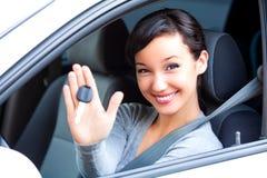 Chaves do carro da posse do motorista da mulher em seu carro novo imagens de stock
