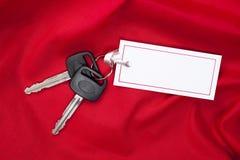 Chaves do carro e cartão do presente no vermelho Foto de Stock