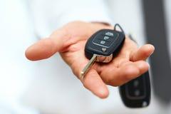 Chaves do carro Mão do vendedor que dá chaves Foto de Stock
