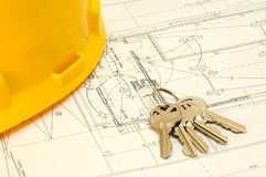 Chaves e chapéu sobre uma planta da construção Imagens de Stock