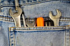 Chaves e chaves de fenda diferentes em um bolso do brim azul Imagem de Stock