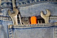 Chaves e chaves de fenda diferentes em um bolso do brim azul Foto de Stock Royalty Free