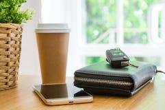 Chaves e documentos do carro, telefone esperto e xícara de café a ir em uma tabela de madeira fotos de stock