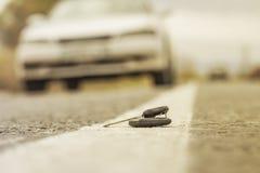 Chaves perdidas do carro que encontram-se na estrada, em um fundo borrado com efeito do bokeh fotografia de stock royalty free
