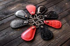 Chaves unidas ao keychain de couro, no fundo de madeira Imagens de Stock