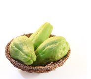 Chayote squash, also known as choko in wooden basket on white Stock Photo