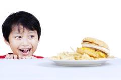 Chciwości chłopiec patrzeje fast food Zdjęcia Royalty Free