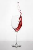 Chełbotanie i poruszający czerwone wino w wineglass pozyci przeciw lekkiemu tłu z odbiciem na stojaku Obrazy Royalty Free