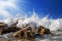 Chełbotanie woda morska na skałach na jaskrawym niebieskim niebie Fotografia Royalty Free