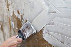 Che allinea la parete i pittori il mastice, pittore passa lo spatul dell'acciaio della tenuta Immagini Stock Libere da Diritti