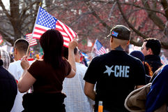 Che and American flag. Woman holding American flag next to man wearing a Che t-shirt and a Cuban flag cap at a pro immigration rally Stock Images