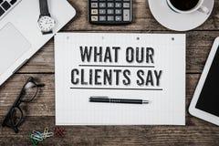 Che cosa i nostri clienti dicono la dichiarazione sul blocco note sulla scrivania dall'ab immagini stock