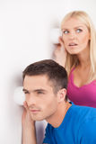 Che cosa sta accendendo là fuori? Belle giovani coppie che ascoltano di nascosto Immagini Stock