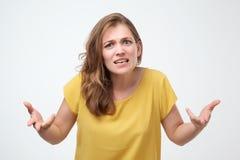 Che cosa voi vogliono da me il concetto ritratto della giovane donna emozionale arrabbiata insoddisfatta in maglietta gialla fotografia stock libera da diritti