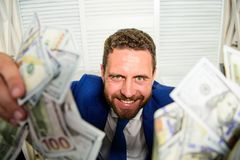 Che k out my profit this month. Earn money easy business tips. Man cheerful happy businessman with pile dollar banknotes. Profit and richness concept stock photography