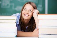 Che sorride With Stack Of dell'insegnante i libri cerca Fotografia Stock