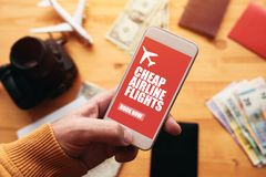 Cheap airline flights online mobile app. Man holding smartphone with mock up application screen related to holiday vacation journey trip stock photos