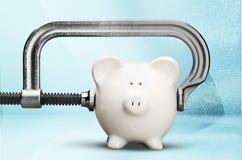 Cheap. Piggy bank recession vise grip coin bank clamp physical pressure stock photos