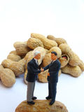 Cheap deal. Two miniature people negociate a cheap contract on peanut stock photo