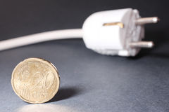 Cheap energy. 20 euro cent coin infront of an electric cable - for concepts like cheap energy or energy savings - focus is on the 20 cents royalty free stock photography