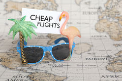 Cheap flights / Cheap plane tickets. Cheap flights note on sunglasses over world map background. Cheap plane tickets, travel tickets concept Stock Images