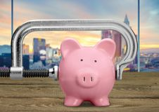 Cheap. Piggy bank recession vise grip coin bank clamp physical pressure royalty free stock photo