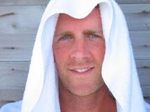 Cheap Sunblock. Handsome man with blue eyes and tan wearing a white towel over his head Royalty Free Stock Photography