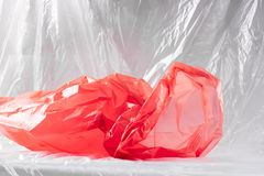 Disgusting crumpled red plastic trash package presenting state of our nature. Cheap thin material. Disgusting crumpled red plastic trash package presenting state stock photo