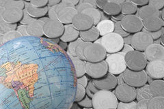 Cheap Trip. Photo of Cheap Trip - Bunch of coins and a globe Stock Image