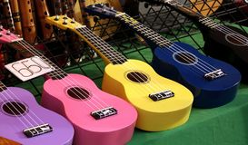 Cheap Ukulele Instruments for Sale at a Market. Colorful ukuleles on sale at an outdoor stall Royalty Free Stock Photo