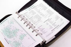 Cheat Sheets. Personal planner open to tables and maps showing conversion tables, time zones and similar information Stock Image