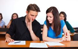 Cheater. Friends cheating, whispering to each other during exam in college stock photography