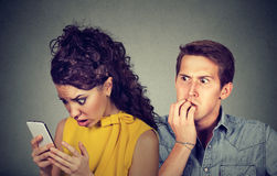 Cheating boyfriend. Man nervously biting fingernails while shocked girlfriend reading text messages on his mobile phone. A cheating boyfriend. Anxious men Royalty Free Stock Images