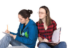 Cheating homework teen. Two teenage girls doing homework together on a white background, one is looking over the other's shoulder, cheating Stock Photos