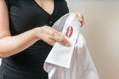 Cheating and infidelity concept. Woman holds white shirt of her husband with red lipstick stains. Stock Photos