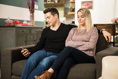 Cheating man caught by girlfriend. Sneaky young men texting his lover while sitting next to his girlfriend at home stock photo