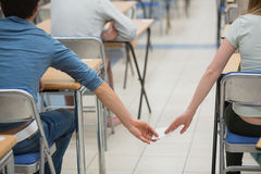 Cheating students in a classroom Stock Images