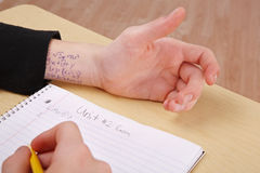 Cheating on a test. A person is at a desk taking a test and they have the answers written on their wrist royalty free stock photo