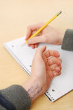 Cheating on a test. A close up of a teenagers hands that has the answers to his test written on his arms stock photography