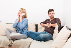 Cheating wife talking privately on the phone. While husband waits on the sofa royalty free stock photo
