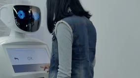 Cheboksary, Rússia - 26 de setembro de 2017: Cidade dos robôs Uma jovem mulher escreve em uma exposição do robô filme
