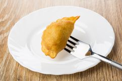 Cheburek strung on fork above white plate on table. Cheburek strung on fork above white plate on wooden table Royalty Free Stock Images