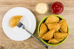 Cheburek strung on fork in plate, ketchup, mayonnaise and bowl. With chebureks on wooden table. Top view Royalty Free Stock Image