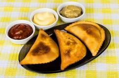 Chebureks fritados no prato e bacias com molhos diferentes Foto de Stock